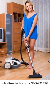 Ordinary young russian housewife in casual hoovering at home and smiling