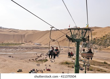 ORDOS, CHINA - OCTOBER 3, 2012: Tourists riding the cable car in Kubuqi desert park, the cable car takes riders to the top of the desert. Kubuqi desert is a tourist's attraction in Inner Mongolia.