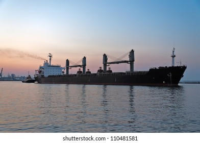 The ore carrier heaves out of the harbor on a tow, the photo is taken at sunset.