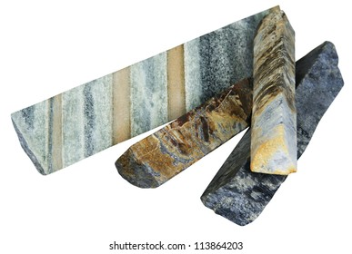 Ore samples in a well core on a white background