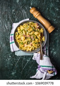Orecchiette pasta with peas and bacon with creamy sauce. Flat lay