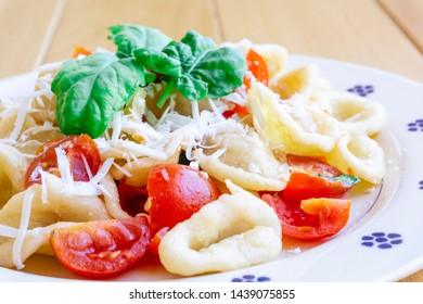 Orecchiette with tomato, fresh basil and fresh cheese (cacioricotta) in a plate on a wooden table. Orecchiette are a typical dish of Puglia (southern Italy)