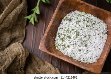 Oregano Herb Salt in Small Wooden Bowl; Fresh sprig of herb on Wooden Tabletop beside the bowl