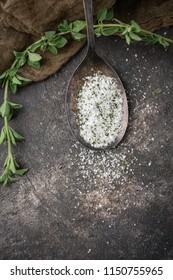 Oregano Herb Salt in Tarnished Spoon on Black Background with Fresh Sprig of Oregano