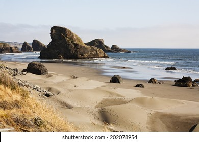 The Oregon coast sand dunes in the front with brown grass and footprints. mid picture the beach with some water and rocks. Back the large rocks that hug the coast line. Waves in the ocean cloudy day.