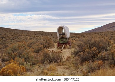 Oregon Trail Covered Wagon. The trail cut by pioneers more than 150 years ago runs through a sagebrush filled valley in eastern OR near Baker City & still has ruts made by the settler's wagon wheels.