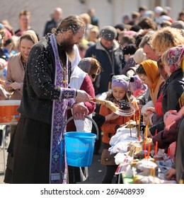 Orel, Russia, April 11, 2015: Traditional orthodox paschal ritual - priest blessing easter eggs and kulitches with holy water square