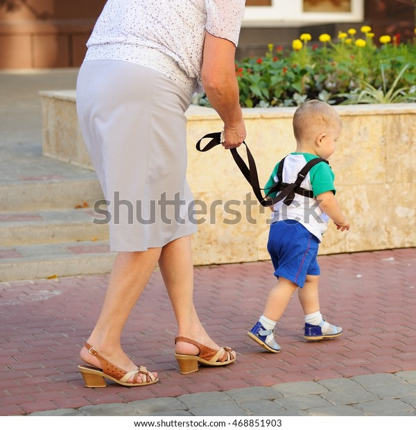 Orel, Russia - August 05, 2016: Orel city day. Woman walking with toddler on leash