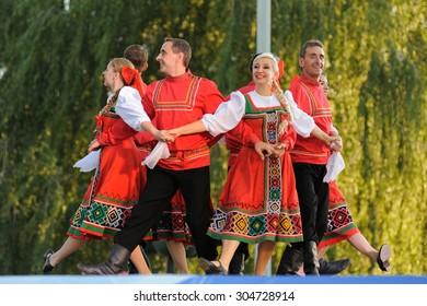 Orel, Russia, August 4, 2015: Orlovskaya Mozaika folk festival, men and women in red Russian suits dancing in the scene