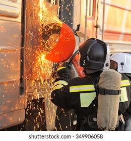 Orel, Russia - December 09, 2015: Emergency Control Ministry (MCHS) tactical exercise. Russian rescue team cutting carriage door with circular saw
