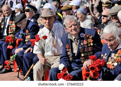 Orel, Russia - May 09, 2015: Celebration of the 70th anniversary of the Victory Day (WWII). War veterans in uniform sitting in the sun with flowers
