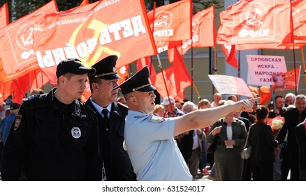 Orel, Russia - May 1, 2017: May demonstration. Policemen in front of crowd with red Communist flags