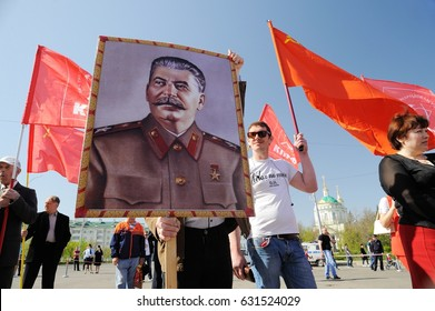 Orel, Russia - May 1, 2017: May demonstration. Young men with Stalin portrait and red Communist flags