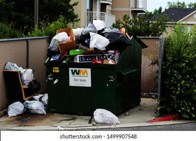 Orem, Utah/United States of America-August 8, 2019:  The overflowing dumpster of trash during move-out and move-in day, around student housing in Orem, Utah with logos and text.