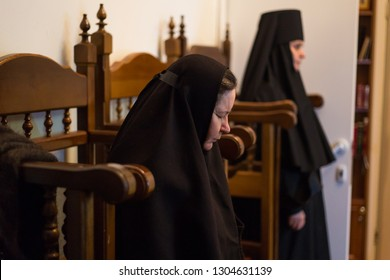 Orenburg, Russian Federation-5 Dec 2018. at the Liturgy, Orthodox nun, closing his eyes, praying sitting on a pedestal of wood on the background of another nun. he nun prays. a woman prays