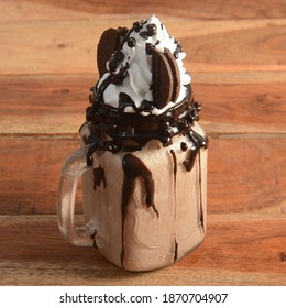 Oreo biscuit Milkshake, blended with oreo biscuits and icecream and topped with ice cream, served in a glass over a rustic wooden background, selective focus on top
