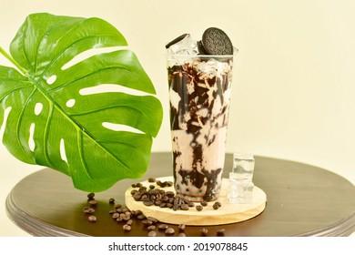 Oreo Milk Bubble Tea - A plastic glass of fresh oreo milk bubble tea on wooden table, Taiwanese drinking culture