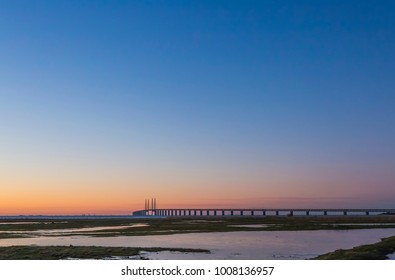 The Oresund bridge between Copenhagen Denmark and Malmo Sweden from the flooded meadows on the beach at Malmo when sunset in January