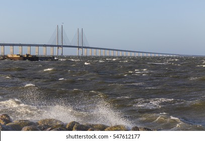 The Oresund bridge and the storm Urd on Oresund between Denmark and Sweden with crashing waves against the beach on the Swedish side
