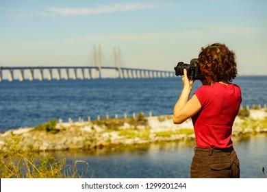 Oresundsbron. Tourist woman taking photo with camera from the Oresund bridge link between Denmark and Sweden Europe, Baltic Sea. Landmark and travel.