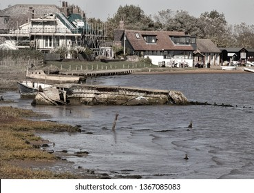 Orford, Suffolk/UK - September 28th 2018 : Old wrecked boats and house renovation in Ore Estuary with view of tourists at riverside cafe in Orford Quay.