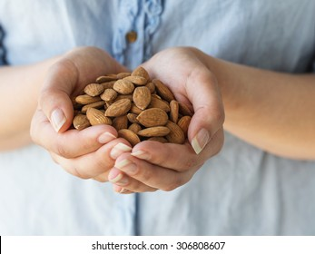 Organic Almonds. The hands of a woman holding whole almonds.