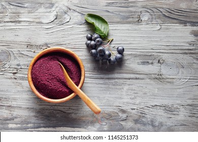 Organic Aronia powder in a bowl with fresh aronia berries on table.
