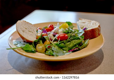 An organic arugula and baby lettuce salad on a dish with fresh baked bread and shallow depth of field