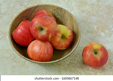 Organic Autumn Glory apples in wooden bowl on rustic stone background in horizontal format