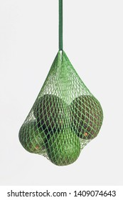 organic avocado in green mesh bag on white background