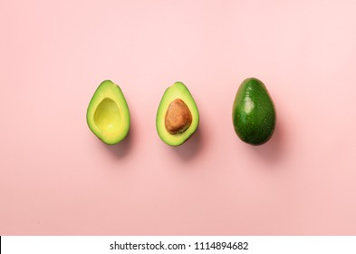 Organic avocado with seed, avocado halves and whole fruits on pink background. Top view. Pop art design, creative summer food concept. Green avocadoes pattern in minimal flat lay style