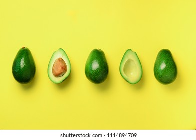 Organic avocado with seed, avocado halves and whole fruits on yellow background. Top view. Pop art design, creative summer food concept. Green avocadoes pattern in minimal flat lay style