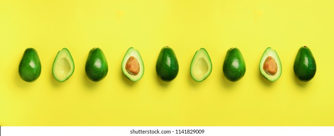 Organic avocado with seed, avocado halves, whole fruits on yellow background. Top view. Banner, seamless pattern. Pop art design, creative summer food concept. Green avocadoes, minimal flat lay style