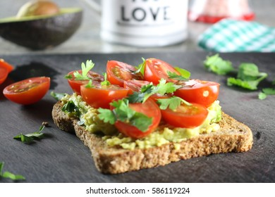 Organic avocado toast topped with organic tomatoes and fresh cilantro.