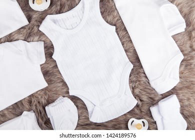Organic baby clothing on fur background. Knolling of body suit, socks, mittens, singlets & pacifier.