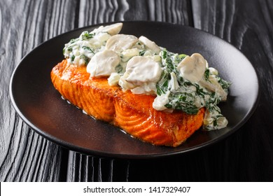 Organic baked salmon fillet topped with creamy spinach, garlic and mushrooms close-up on a plate on the table. horizontal