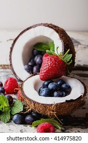 Organic berries: blueberries and strawberries served in two coconuts on a light wooden rustic, background. Concept of healthy food. Top view. Selective Focus