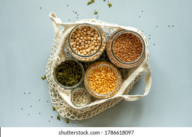 Organic bio bulk products in zero waste shop. Foods storage in kitchen at low waste lifestyle. Cereals and grains in glass jars on table. Eco friendly shopping in plastic free grocery store.
