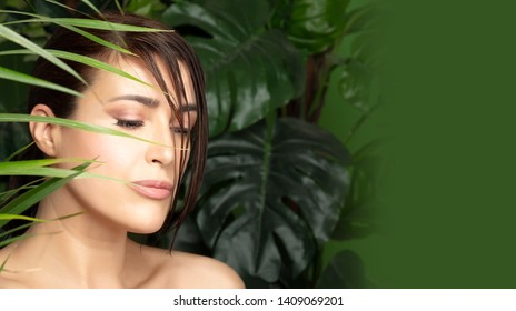Organic and bio cosmetics concept with the face of a beautiful young woman with flawless skin and downcast eyes surrounded by fresh tropical leaves over a green background and copy space