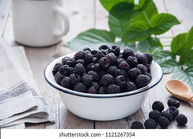 Organic Black raspberry in a white enamel plate on a gray wooden background