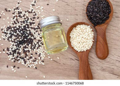 organic Black and white sesame seeds in wooden spoon with oil bottle , top view or overhead shot