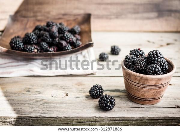 organic blackberries in pottery on a gray wooden board, rustic