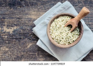Organic blanched hemp seeds in a bowl on old wooden table. Healthy eating supplement. Superfood concept. Top view. Copy space.
