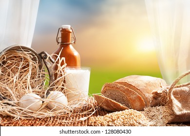 organic breakfast concept with fresh eggs,milk and bread in front of a open window with a beautiful landscape at background
