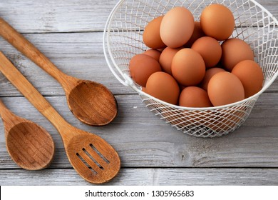 Organic Brown Eggs in white basket with wooden spoons