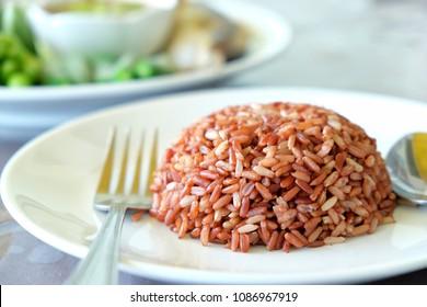 Organic brown rice in dish, a dish of brown rice, cooked brown rice in a dish, white dish with cooked brown rice.