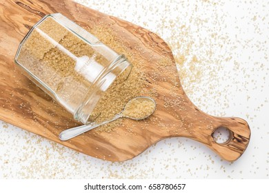Organic brown sugar in glass jar on wooden chopping board. Top view.