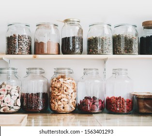 Organic bulk products in zero waste shop. Foods storage in kitchen at low waste lifestyle. Dried berries and fruits in glass jars on shelves. Eco friendly shopping in plastic free grocery store. - Shutterstock ID 1563401293