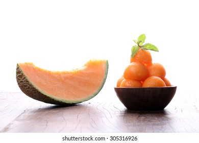 Organic cantaloupe melon in wooden bowl isolated on white background.