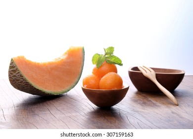 Organic cantaloupe melon in wooden spoon on wooden table.